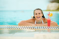 Smiling young woman relaxing in pool with cocktail Stock Photos