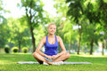 Smiling young woman resting on a mat in a park an exercise Royalty Free Stock Photo