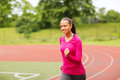 Smiling young woman running on track outdoors fitness sport training and lifestyle concept african american Royalty Free Stock Images