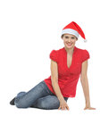 Smiling young woman in Santa hat sitting on floor Royalty Free Stock Photo