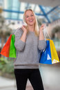 Smiling young woman shopping in a store or mall buying Royalty Free Stock Image