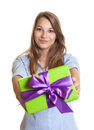 Smiling young woman showing a christmas gift attractive with long blond hair her for on white background Stock Photo