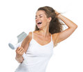 Smiling young woman singing while blow dry isolated on white Royalty Free Stock Photography