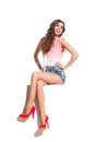 Smiling young woman sitting with legs crossed in pink top jeans shorts and red high heels on the top of white banner at knee Royalty Free Stock Photo