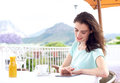 Smiling young woman sitting at outdoor cafe with digital tablet Royalty Free Stock Photo