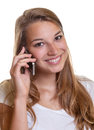 Smiling young woman on the smartphone with blonde hair a white background is happy about news phone Royalty Free Stock Photography