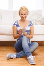 Smiling young woman with smartphone at home technology and internet concept sitting on couch Stock Photography