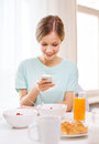 Smiling young woman with smartphone reading news food home and technology concept and having breakfast at home Royalty Free Stock Image