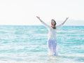 Smiling young woman standing in sea and sprinkling water Royalty Free Stock Photo