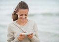 Smiling young woman in sweater on beach writing sms with long hair Royalty Free Stock Image