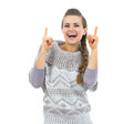 Smiling young woman in sweater pointing up on copy space