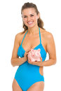 Smiling young woman swimsuit holding piggy bank isolated white Royalty Free Stock Photo