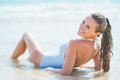 Smiling young woman in swimsuit laying at seaside rear view pretty white Stock Images