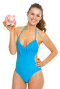 Smiling young woman in swimsuit showing piggy bank isolated on white Royalty Free Stock Photos