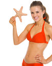 Smiling young woman swimsuit showing starfish isolated white Royalty Free Stock Images