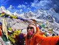 Smiling young woman takes a selfie on mountain peak Kala Patth