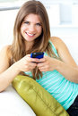 Smiling young woman texting sitting on the sofa Stock Images