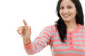 Smiling young woman touching imaginary screen with her finger Stock Photos