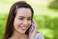 Smiling young woman using her mobile phone Royalty Free Stock Images