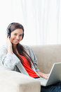 A smiling young woman using a laptop and headphones while lookin Stock Photography
