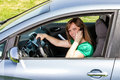 Smiling young woman using smart phone while driving her car Royalty Free Stock Photography