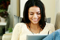 Smiling young woman using tablet computer at home and looking on it Royalty Free Stock Photo