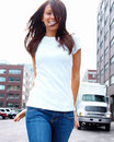Smiling young woman walking down street Royalty Free Stock Images