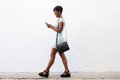 Smiling young woman walking and looking at cell phone Royalty Free Stock Photo