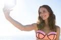 Smiling young woman wearing bikini while taking selfie at beach Royalty Free Stock Photo