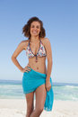 Smiling young woman wearing a blue sarong in front of the sea Royalty Free Stock Images