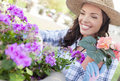 Smiling young woman wearing hat gardening outdoors attractive happy adult Stock Photography