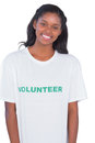 Smiling young woman wearing volunteer tshirt on white background Royalty Free Stock Photography