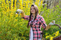 Smiling young woman with wicker basket full of yellow flowers garden concept Stock Photo