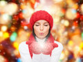 Smiling young woman in winter clothes happiness holidays christmas and people concept red hat scarf and mittens over lights Stock Photo