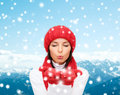 Smiling young woman in winter clothes happiness holidays tourism travel and people concept red hat and mittens over snowy Royalty Free Stock Photo