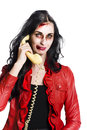 Smiling zombie woman talking on a retro corded telephone Stock Photo