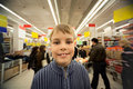 Smilling boy stand in centre in supermarket Royalty Free Stock Image