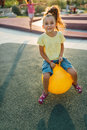 Smilling girl is jumping on the ball Royalty Free Stock Photo