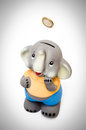 Smilling sweet elephant piggy bank coin falling Royalty Free Stock Image