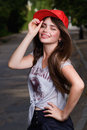 Smilling teen model beautiful on street red cap grey t shirt dark blue shorts Royalty Free Stock Photography