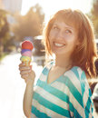 Smilling woman holding ice cream cone in her hands outdoors Royalty Free Stock Image