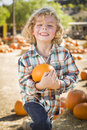 Smilng boy holding his pumpkin at a pumpkin patch adorable little sitting and in rustic ranch setting the Royalty Free Stock Image