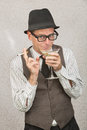 Smirking man sipping martini businessman with hat and eyeglasses drinking alcohol Stock Image