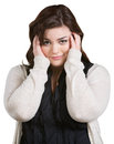 Smirking young woman with hands on ears over white Royalty Free Stock Images
