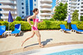 Smling woman in pink sportswear runs along pool young Stock Photos