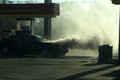 Smoke from car fire rolling fine at gas station Stock Image