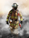 Smoke eater a firefighter pierces through a wall of searching for survivors Stock Image