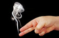 Smoke from the fingers of a hand depicting weapons gun photo on black background Stock Image