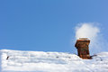 Smoke out of a brick chimney on a snowy rooftop Royalty Free Stock Photo