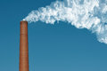 Smoke stack over a blue sky background Royalty Free Stock Photos